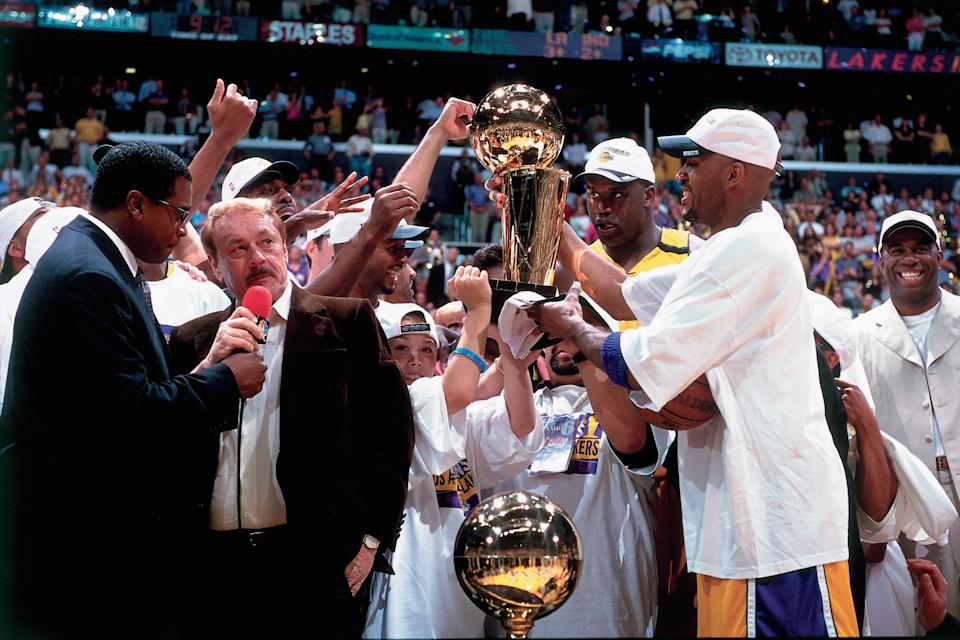 Los Angeles Lakers owner Jerry Buss is interviewed by sportscaster Ahmad Rashad while his team celebrates winning the NBA Championship after defeating the Indiana Pacers in Game Six of the 2000 NBA Finals on June 19, 2000 at the Staples Center in Los Angeles, California. (Photo by Andrew D. Bernstein/NBAE via Getty Images)