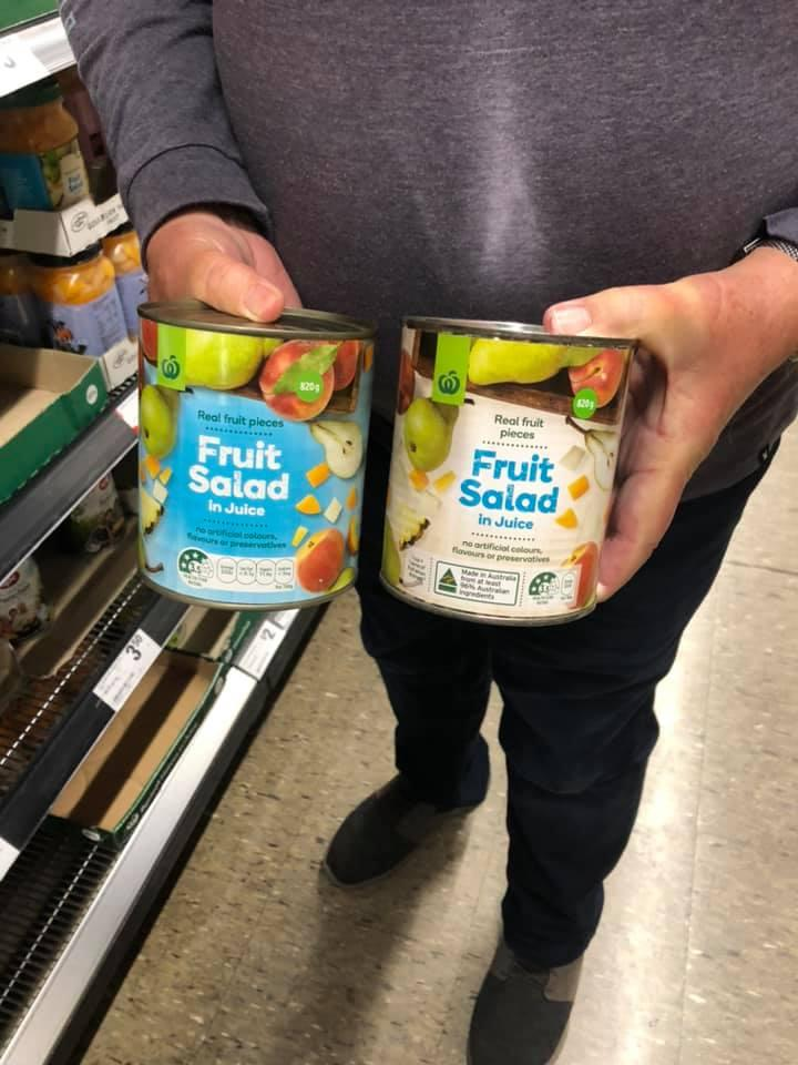 Person holding two Woolworths canned fruit salads.