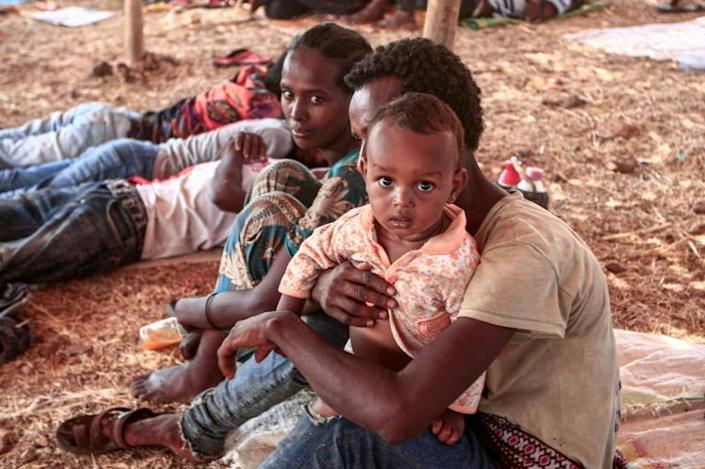 An Ethiopian refugee who fled fighting in Tigray province sits holding a child in a hut at Um Raquba camp in Sudan's eastern Gedaref province on November 16, 2020