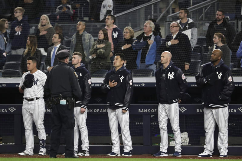 "New York Yankees players listen to ""God Bless America"" during the seventh-inning stretch of the team's baseball game against the Kansas City Royals, Thursday, April 18, 2019, in New York. The Yankees have suspended the use of Kate Smith's recording of the song while they investigate an allegation of racism against the singer. The New York Daily News reported there are conflicting claims about Smith's 1939 song ""That's Why Darkies Were Born."" The song originated in the 1931 Broadway review ""George White's Scandals,"" and was considered satire. It was recorded by Smith and by Paul Robeson, who was black. (AP Photo/Julio Cortez)"