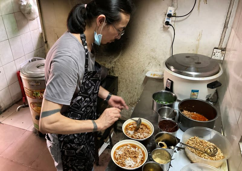 Noodles shop owner and a rock band singer Wang Zongxing makes noodles for customers at his restaurant in Shenzhen