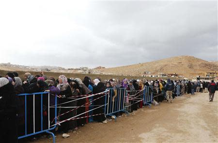 Syrians, fleeing the violence from the Syrian town of Qara, queue to register to get help from relief agencies at the Lebanese border town of Arsal, in the eastern Bekaa Valley