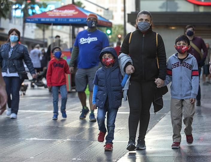 A family wears protective masks during a walk in Hollywood.