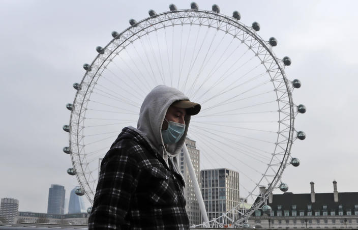 A man wearing a face covering walks past the London Eye in London, Friday, Jan. 8, 2021. Britain's Prime Minister Boris Johnson has ordered a new national lockdown for England which means people will only be able to leave their homes for limited reasons, with measures expected to stay in place until mid-February. (AP Photo/Frank Augstein)