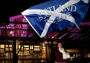 "A supporter from the ""Yes"" Campaign waves a Scottish Saltire flag outside the Scottish Parliament in Edinburgh, Scotland"