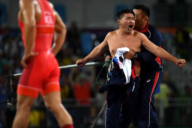 <p>Mongolias coaches protest the judges decision after Mandakhnaran Ganzorig (red) of Mongolia is defeated by Ikhtiyor Navruzov (blue) of Uzbekistan in the Men's Freestyle 65kg Bronze match against on Day 16 of the Rio 2016 Olympic Games at Carioca Arena 2 on August 21, 2016 in Rio de Janeiro, Brazil. (Getty) </p>