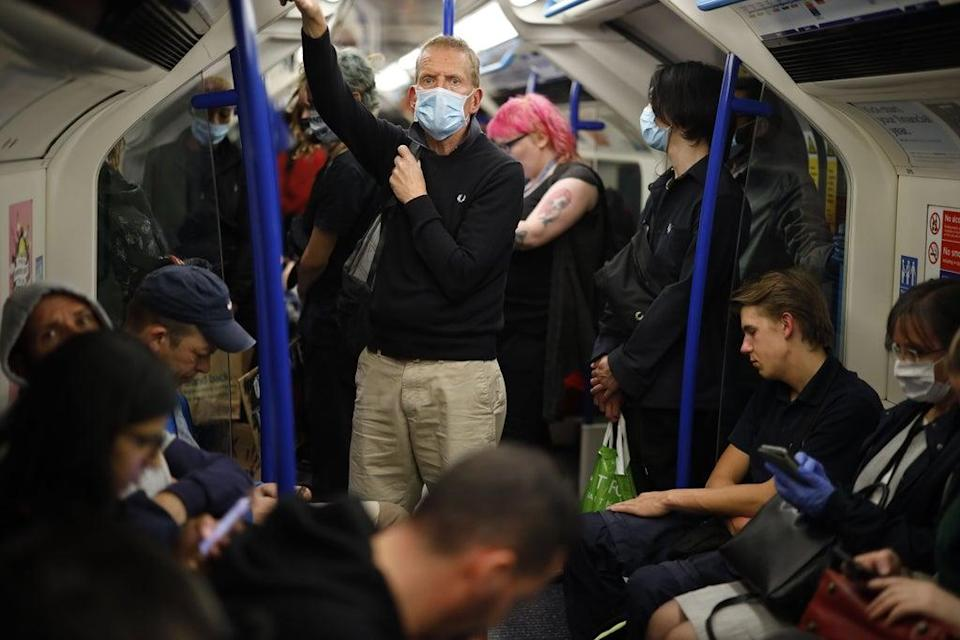 Commuters in masks on the London Underground  (AFP via Getty Images)