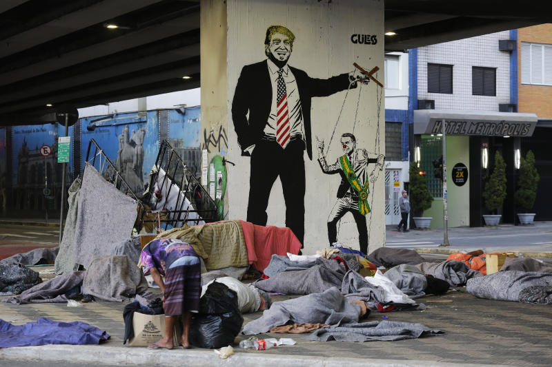 """Homeless people sleep under a bridge in front of a mural depicting U.S. President Donald Trump as a puppeteer manipulating Brazil's President Jair Bolsonaro, in downtown Sao Paulo, Brazil, Tuesday, July 23, 2019. Bolsonaro said last week that severe hunger is not a problem for the country. He acknowledged that things could """"go bad"""" and people might """"not eat well."""" But, he added: """"To speak of starving in Brazil is a big lie."""" (AP Photo/Nelson Antoine)"""