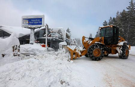 A plow clears snow after a heavy winter storm in Tahoe City, California