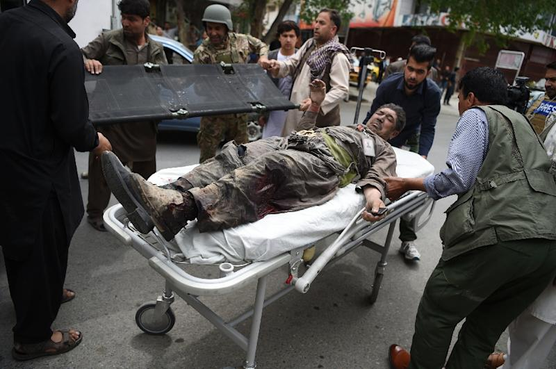 A wounded Afghan man is brought on a stretcher to an Italian aid organization's hospital, as Afghan security forces battled an attack by Taliban militants on a compound housing an international aid organisation in Kabul (AFP Photo/WAKIL KOHSAR)