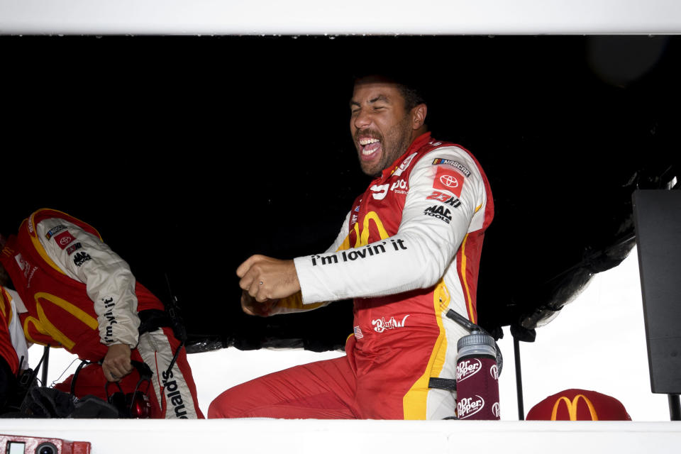 Bubba Wallace reacts after he is pronounced the winner while waiting out a rain delay before which he was the leader during a NASCAR Cup series auto race Monday, Oct. 4, 2021, in Talladega, Ala. (AP Photo/John Amis)