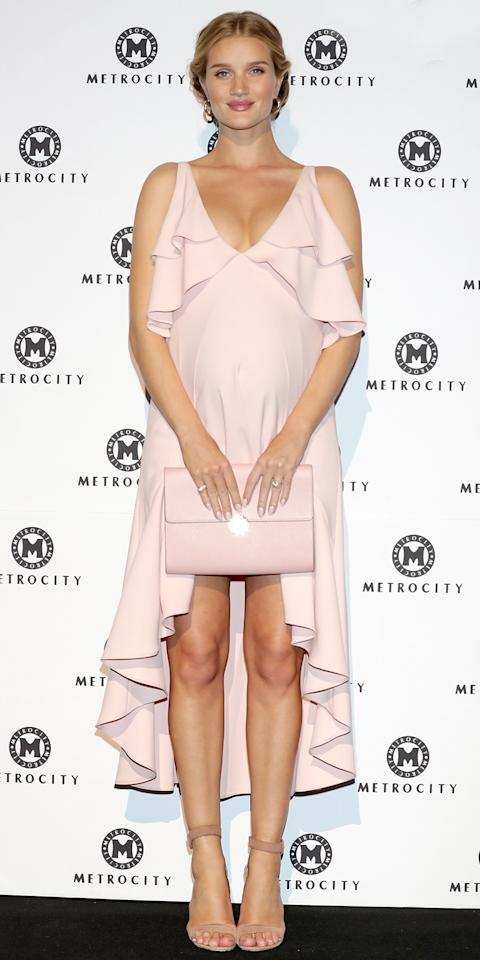 <p>The expectant model looked pretty in pale pink at a photocall during Seoul Fashion Week in South Korea. Huntington-Whiteley's baby bump was on full display in a delicate plunging dress that featured a ruffled bodice and high-low hemline. She completed her look with an oversize matching clutch, nude ankle-strap heels, and gold hoop earrings.</p><p> </p>