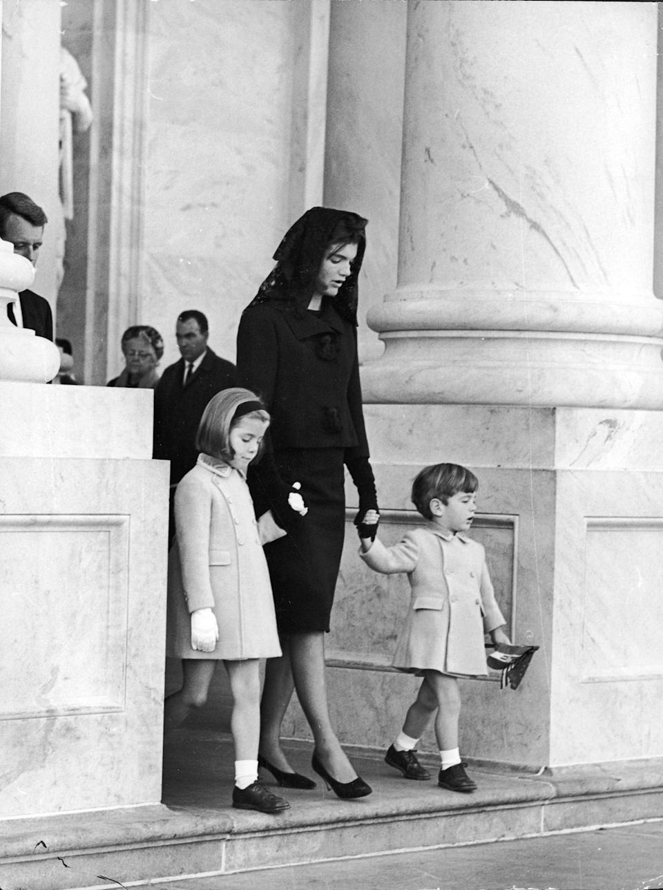 26th November 1963, First Lady Jacqueline Kennedy (1929 - 1994) holds the hands of her two children, John Jr (1960 - 1999) and Caroline, as they leave the White House to attend the Lying-in-State of assassinated President John F Kennedy at the Capitol, Washington, D C. Rober (Photo by Express/Getty Images)