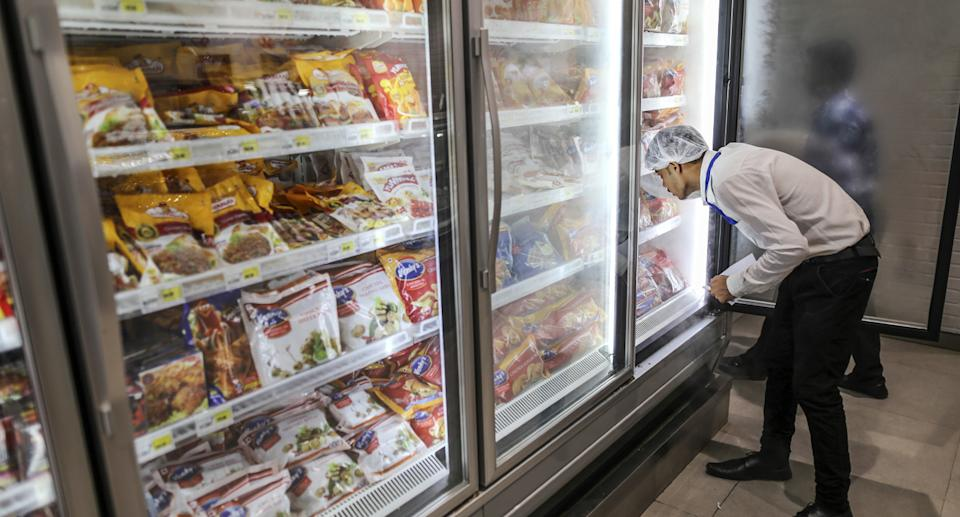 Traces of coronavirus have been detected in imported frozen food and on food packaging in China. Pictured is a man with a hairnet looking into a fridge at a supermarket.