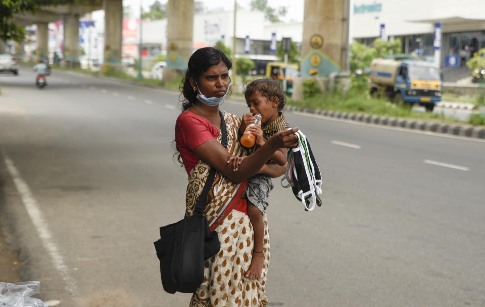 An Indian woman stands carrying her child by a roadside as she sells face masks during lockdown to curb the spread of coronavirus in Kochi, Kerala, India, Saturday, May 16, 2020. Over 90% of India's workforce is employed in the informal sector, without access to significant savings or social protection benefits such as paid sick leave or insurance. (AP Photo/R S Iyer)