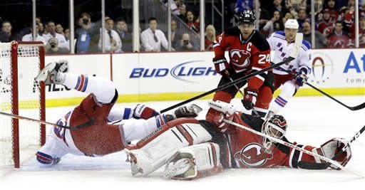 New Jersey Devils goalie Martin Brodeur, bottom right, makes a save on a shot by New York Rangers left wing Rick Nash, left, during the first period of an NHL hockey game, Tuesday, Feb. 5, 2013, in Newark, N.J. (AP Photo/Julio Cortez)