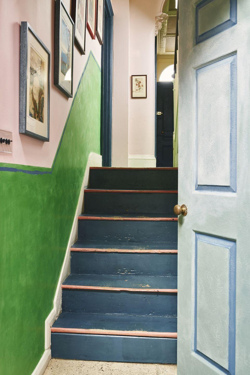 """<p>""""Painting lines to emphasize or even suggest panelling where there isn't any is a quick and easy way to add witty design flair to spaces,"""" says Sloan of her own entryway in her Oxford, England home. """"The stairs have also been painted with Scandinavian Pink because Cubans love a color clash and I wanted this hallway to sing with the colorful charm of Havana, along the runners, sanded back to suggest the romance of rusticity and faded grandeur, then lacquered with Matt Chalk Paint® Lacquer to protect.""""</p><p>The wall is painted in Antoinette and Antibes Green Chalk Paint®, the latter of which is waxed to ensure little hands don't scuff up the paint. The wall also features a thin blue line, painted Aubusson Blue, which matches the panels around the home's front door to create a seamless look.</p>"""