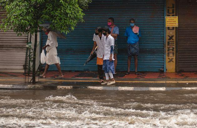 Two medical workers wearing masks as a precaution against the coronavirus assess the water level as they try to cross a flooded street during heavy rainfall in Kochi,, Aug. 7, 2020.