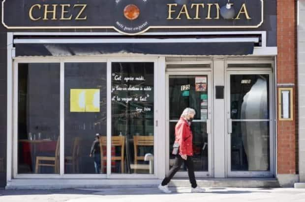 A pedestrian in a mask passes a restaurant on promenade du Portage in downtown Gatineau, Que.'s Hull community in late April 2021.  (Guillaume Lafreniere/Radio-Canada - image credit)