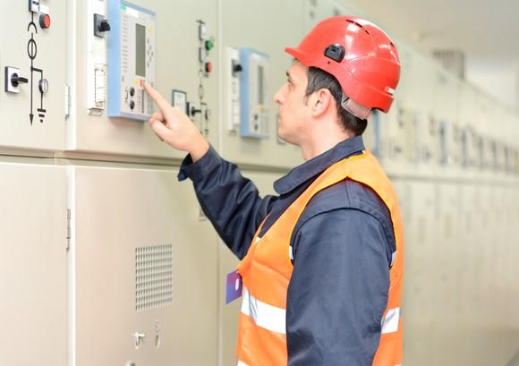 A man examining industrial electric equipment