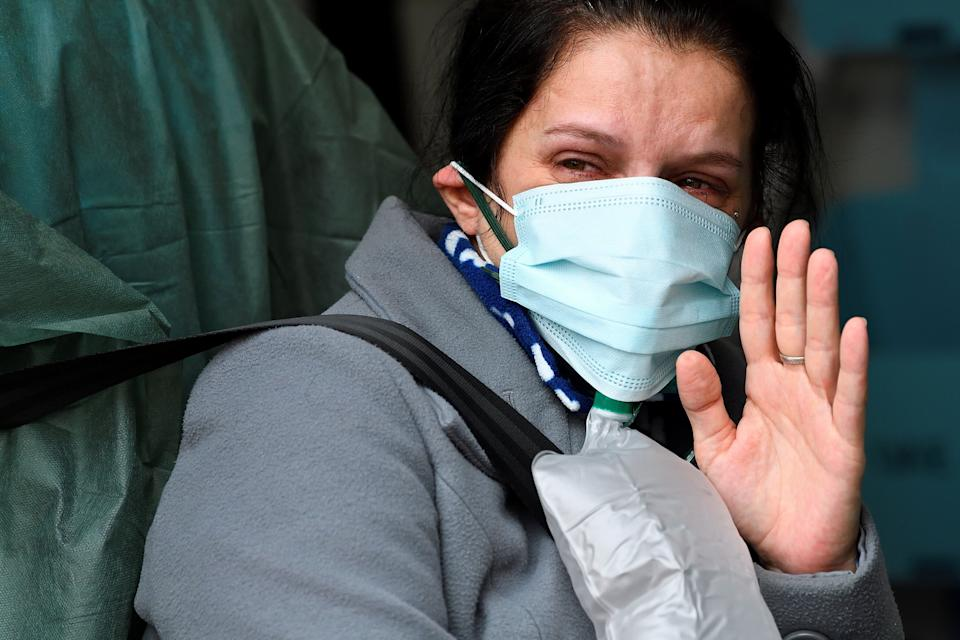 A woman possibly suffering with the coronavirus disease (COVID-19) waves goodbye to her family before being transported to a hospital, inside an ambulance of White Cross, a non-profit organisation, in Arcore, near Monza, Italy November 16, 2020. Picture taken November 16, 2020. REUTERS/Flavio Lo Scalzo     TPX IMAGES OF THE DAY (Photo: Flavio Lo Scalzo / Reuters)