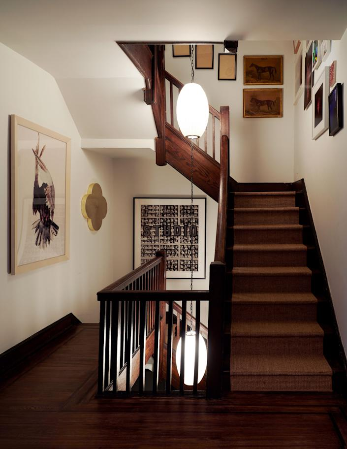 """George Nelson lights hang in the stairwell, which displays photographs by Walker Evans and <a href=""""https://gagosian.com/artists/roe-ethridge/"""">Roe Ethridge</a> and a painting by <a href=""""http://www.maxgimblett.com/"""">Max Gimblett</a>."""