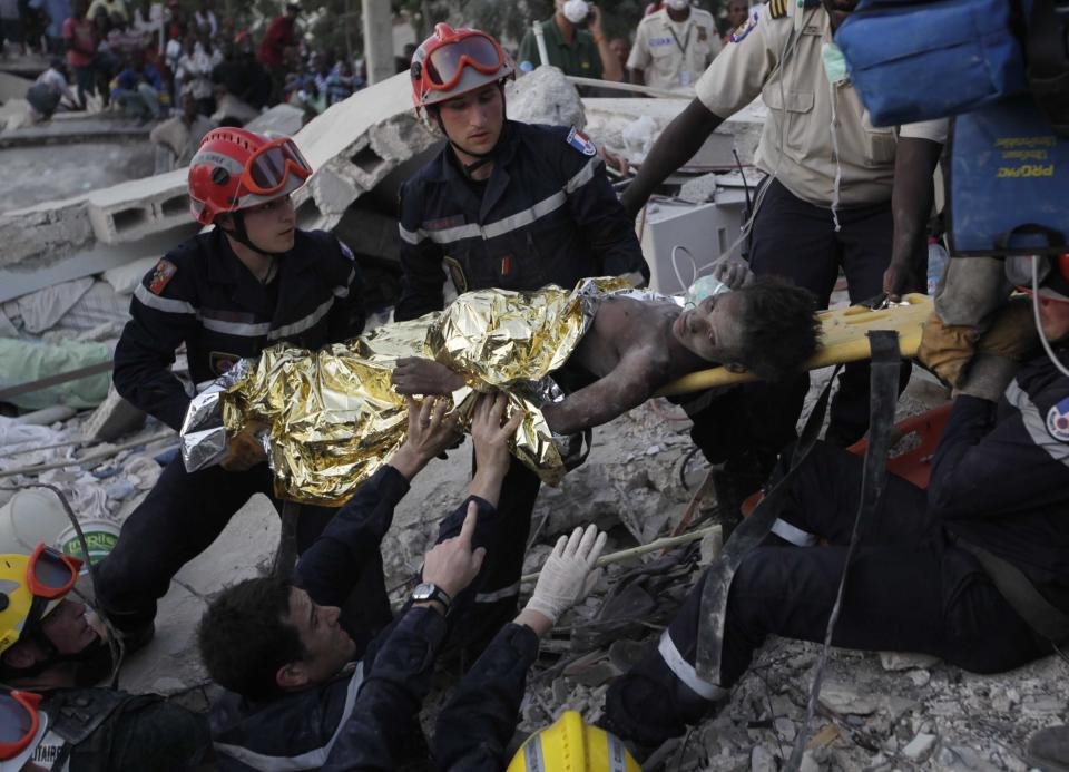 FILE - In this Jan. 27, 2010 file photo, French search and rescue workers pull Darlene Etienne from the rubble of her cousin's home 15 days after the earthquake in Port-au-Prince. Rescuers found her, thirsty and near death. Stories of endurance and longevity under the most dire circumstances continue to kindle hopes that rescuers will find more people alive within the tons of debris that was once the 12-story Champlain Tower condos in Surfside, Fla. (AP Photo/Ramon Espinosa, File)