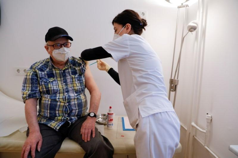 FILE PHOTO: A doctor delivers the first dose of the Pfizer-BioNTech vaccine against the coronavirus to an 84-year-old man in Berlin, Germany