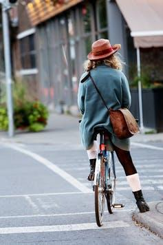 Woman in a hat on a bicycle, shot from behind