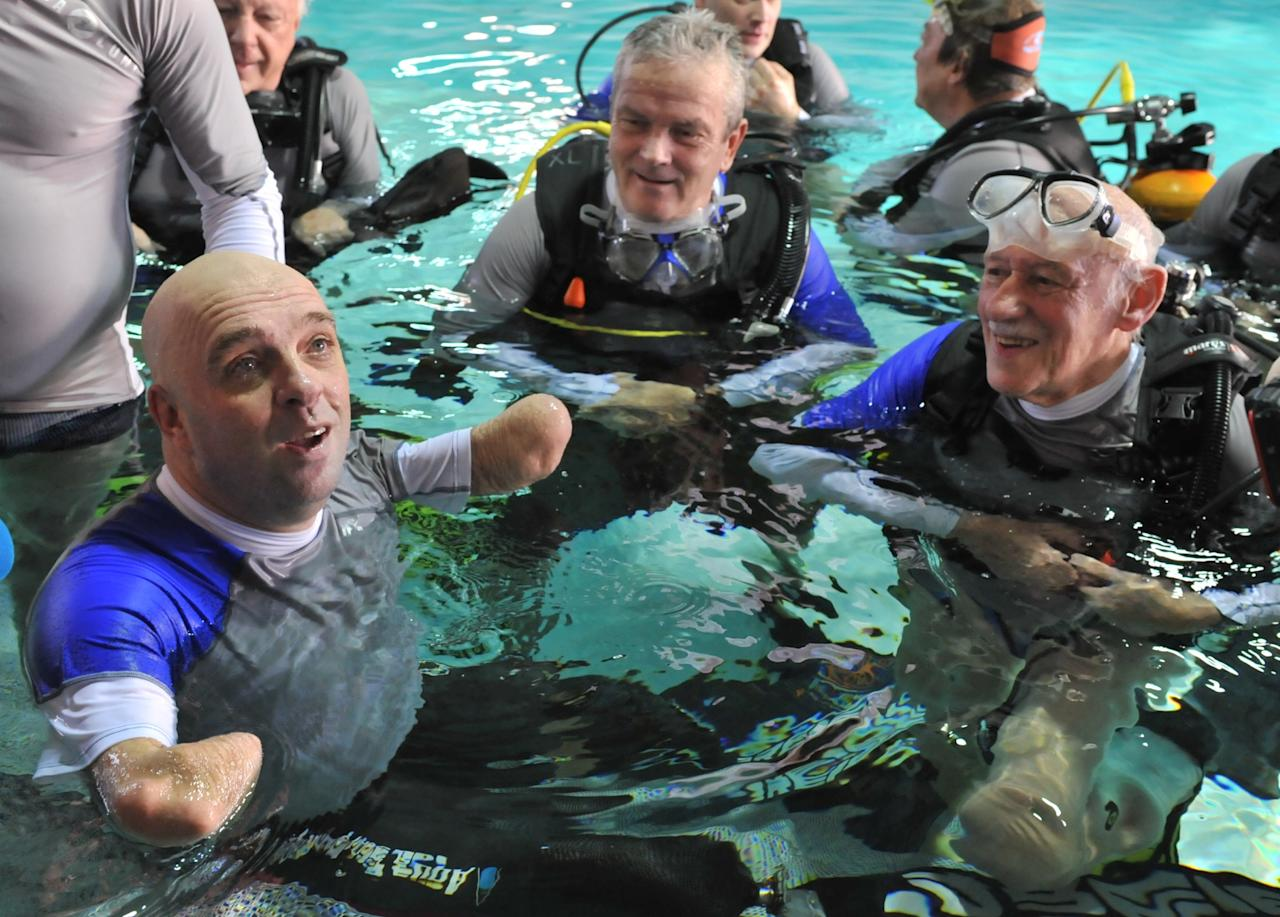 French Philippe Croizon (L), 44, celebrates on January 10, 2013with a group of 15 Belgian divers after becoming the first quadruple amputee to dive at a depth of 33 meters in the deepest swiming pool in the world in Brussels. He used flippers attached to prosthetic limbs to dive to the bottom of the pool to set a new world record for an amputee.   Croizon had all four limbs amputated in 1994 after being struck by an electric shock of more than 20,000 volts as he tried to remove a TV antenna from a roof. He has swum across the English Channel and all five intercontinental channels.  AFP PHOTO  GEORGES GOBETGEORGES GOBET/AFP/Getty Images