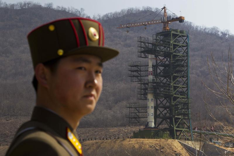 "FILE - In this Sunday, April 8, 2012 file photo, a North Korean soldier stands in front of the country's Unha-3 rocket, slated for liftoff between April 12-16, at a launching site in Tongchang-ri, North Korea. According to North Korea's official version of things, commemorated on postage stamps and re-enacted in mass performances, the country's first venture into space was 14 years ago, when the ""Bright Shining Star 1"" satellite roared into orbit and began broadcasting marching music praising Kim Il Sung. (AP Photo/David Guttenfelder, File)"