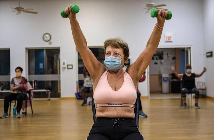 Elma Hamblet Bastien, center, lift her arms while working with weights during the Medicare Advantage program that offers up Silver Sneakers fitness classes on Tuesday, October 20, 2020 at the Alper Jewish Community Center in Kendall, Florida.
