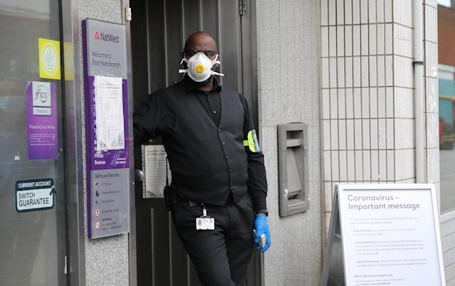 A security man wearing protective personal equipment controls a queue outside a branch of Natwest Bank in East Ham, east London. (PA)