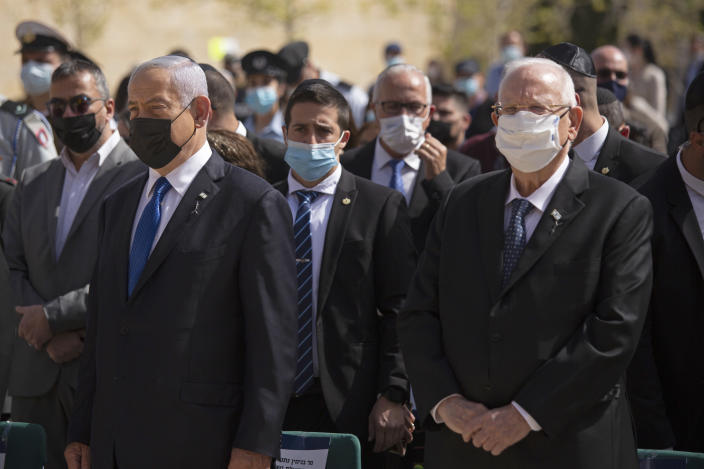 Israeli Prime Minister Benjamin Netanyahu, left, stands next to President Revin Rivlin as they attend a ceremony marking the annual Holocaust Remembrance Day, at Yad Vashem Holocaust Memorial in Jerusalem, Thursday, April 8, 2021. (AP Photo/Maya Alleruzzo, Pool)