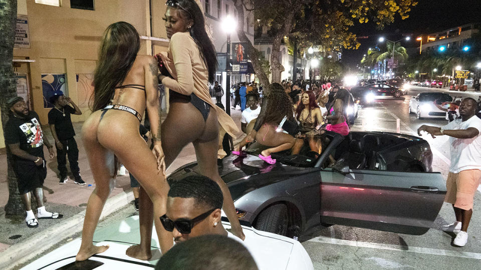A large crowd of people, pictured here at a party on the street in Miami Beach.