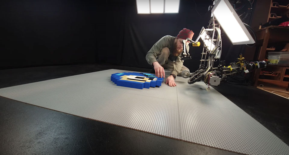 An artist and musician laying out LEGO pieces on the floor in front of a camera and lighting setup for an 8-Bit-Style LEGO Stop-Motion
