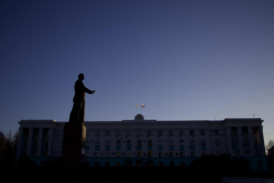 """FILE - In this Saturday, March 15, 2014 file photo, the Russian and Crimean flags fly on a local government building as a statue of Soviet revolutionary leader and founder Vladimir Lenin is silhouetted by the setting sun in Simferopol, Ukraine. Despite the pebble beaches and cliff-hung castles that made Crimea famous as a Soviet resort hub, the Black Sea peninsula has long been a corruption-riddled backwater in economic terms. The Kremlin, which decided to take the region from Ukraine after its residents voted in a referendum to join Russia, has begun calculating exactly what it will cost to support Crimea's shambolic economy _ which one Russian minister described as """"no better than Palestine."""" (AP Photo/Ivan Sekretarev, File)"""