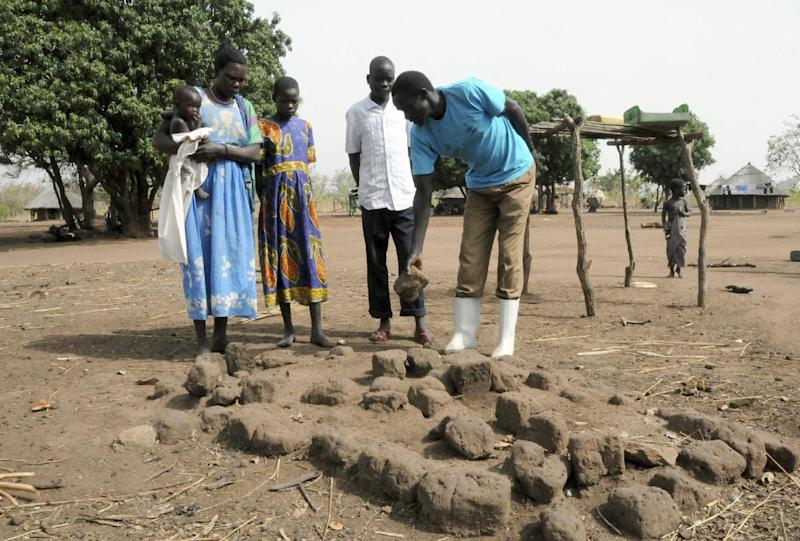 In this photo taken Monday Feb. 20, 2012, a Ugandan family shows the grave of a family member who died of nodding disease in Kitgum district, Uganda. Uganda this week hosts a four-day international conference on nodding syndrome that health officials believe will lead to a clearer understanding of the mysterious disease. The disease is calling nodding syndrome, or nodding head disease, because those who have it nod their heads and sometimes go into epileptic-like fits. The disease stunts children and destroys their cognition, rendering them unable to perform small tasks. (AP Photo/Stephen Wandera)