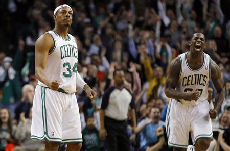 Boston Celtics forwards Paul Pierce (L) and Brandon Bass react after a Celtics basket in the final minutes of their NBA basketball game against the Chicago Bulls in Boston, Massachusetts February 13, 2013. REUTERS/Brian Snyder