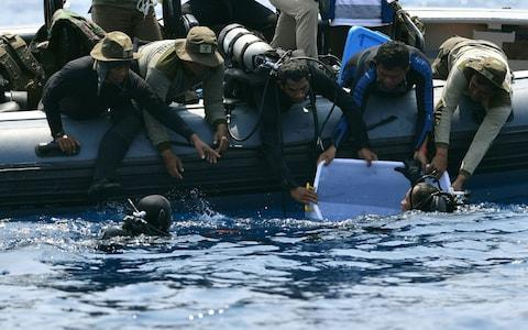 Divers recover the black box from the wreckage of the Lion Air plane - Credit: Adek Berry/AFP