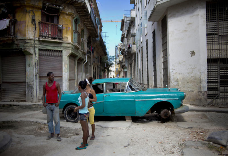 People talk as they stand in a street blocked by a broken down classic car in Havana, Cuba, Thursday, Dec. 26, 2013. The Associated Press recently checked in with nine small business owners whose fortunes it first reported on in 2011 as they set up shop amid the excitement of President Raul Castroís surprising embrace of some free enterprise. Their fates tell a story of divided fortunes. (AP Photo/Ramon Espinosa)
