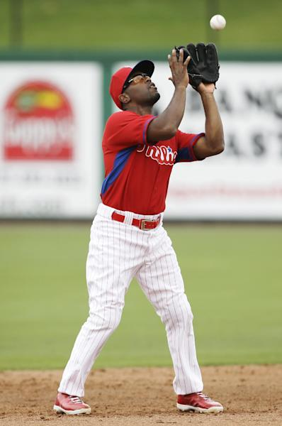 Philadelphia Phillies shortstop Jimmy Rollins catches a fly ball hit by Toronto Blue Jays catcher Dioner Navarro during the second inning of an exhibition baseball game Wednesday, Feb. 26, 2014, in Clearwater, Fla. (AP Photo/Charlie Neibergall)