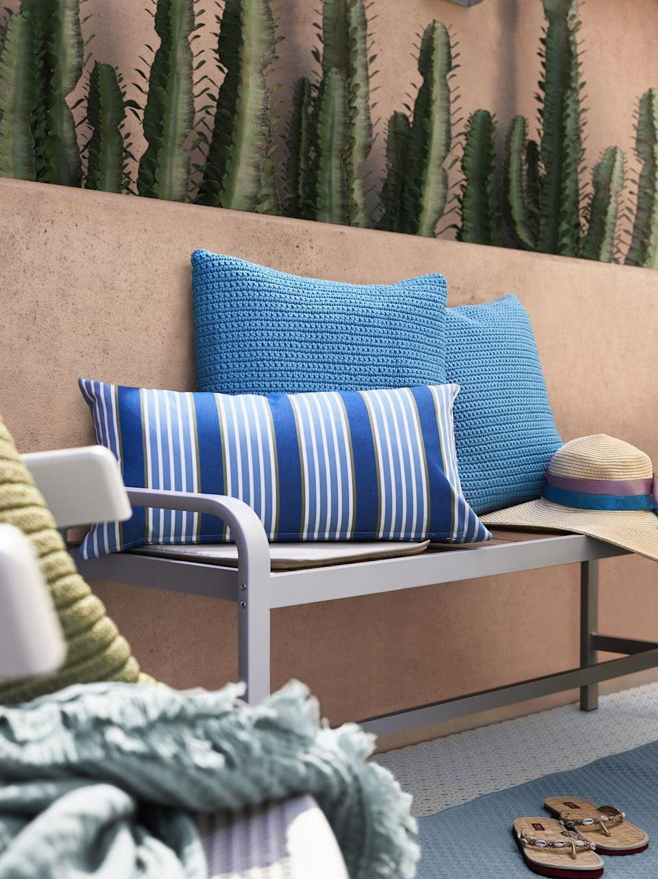 """<p>Spruce up your space with cosy cushions, comforting textures and outdoor rugs. """"Textiles are a quick, easy and affordable way to transform your space and express your personality,"""" adds Rosheen.</p><p>""""Emulate the feeling of a summer blue sky with the handmade SÖTHOLMEN crochet cushion cover. For a bold statement piece, add some fun with the striped FUNKÖN cushion.""""</p>"""