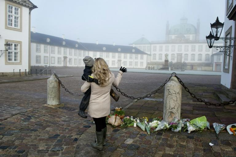 A woman and a child stand by a makeshift memorial of flowers outside Denmark's Fredensborg Palace following the death of Prince Henrik