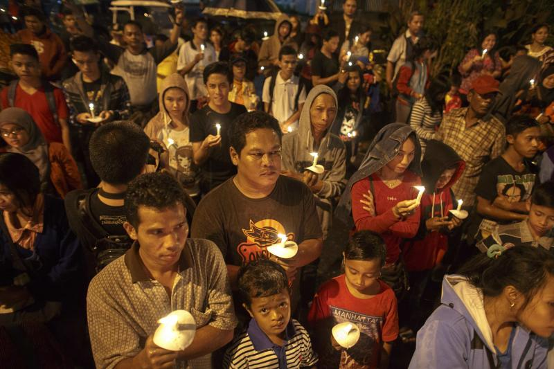 Indonesians hold up candles during a candle light vigil for the victims of AirAsia flight QZ8501 at Surabaya