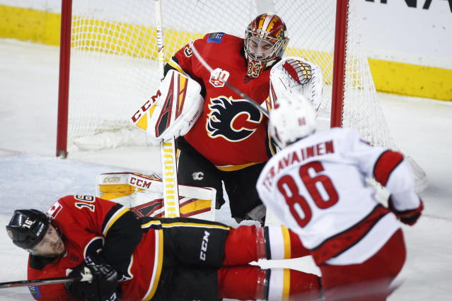 Carolina Hurricanes' Teuvo Teravainen, right, looks on as Calgary Flames goalie David Rittich (33) deflects the puck during first-period NHL hockey game action in Calgary, Alberta, Saturday, Dec. 14, 2019. (Jeff McIntosh/The Canadian Press via AP)