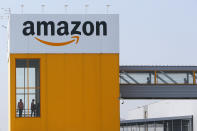 FILE - In this April 9, 2020, file photo, employees observe social distancing due to coronavirus, at the entrance of Amazon, in Douai, northern France. Amazon announced Tuesday, Feb. 2, 2021, that Jeff Bezos would step down as CEO later in the year, leaving a role he's had since founding the company nearly 30 years ago. (AP Photo/Michel Spingler, File)