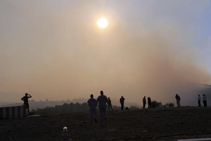 People in Jerusalem gather beneath a sky darkened by wildfire smoke burning for a second day on the outskirts of the city, Monday, Aug. 16, 2021. Israel Fire and Rescue service said in a statement that 45 firefighting teams accompanied by eight planes were working to contain five fires in the forested hills west of the city. (AP Photo/Mahmoud Illean)