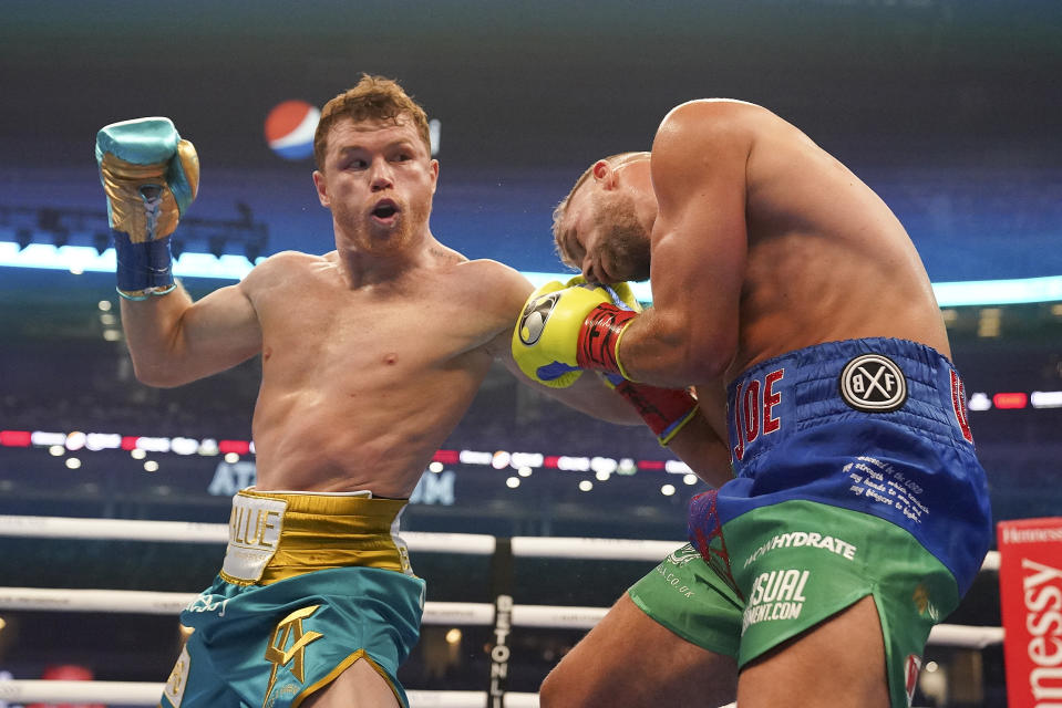 Canelo Alvarez, left, exchanges punches with Billy Joe Saunders during a unified super middleweight world championship boxing match, Saturday, May 8, 2021, in Arlington, Texas. (AP Photo/Jeffrey McWhorter)