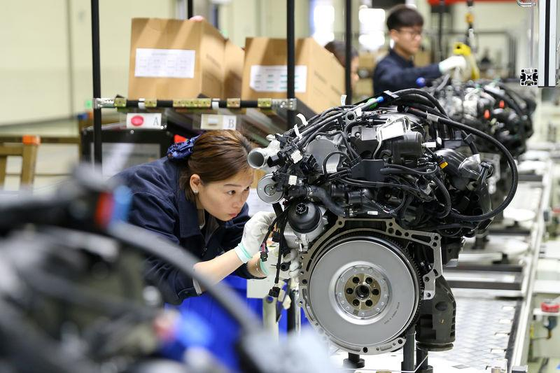 FILE PHOTO: Employees work on the production line at a factory of automotive engine manufacturer Power Xinchen in Mianyang